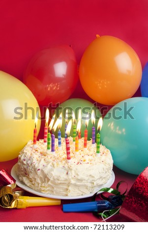 Studio shot of typical birthday set up of cake, hats and party balloons