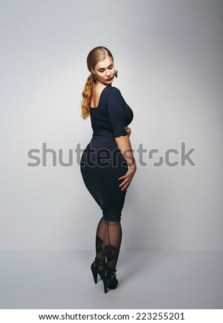 Studio shot of voluptuous woman posing in black dress over grey background.  - stock photo