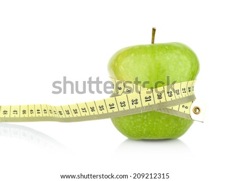 Studio shot of whole green healthy apple with tape measure white background