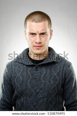 Studio shot of young angry man on gray background - stock photo