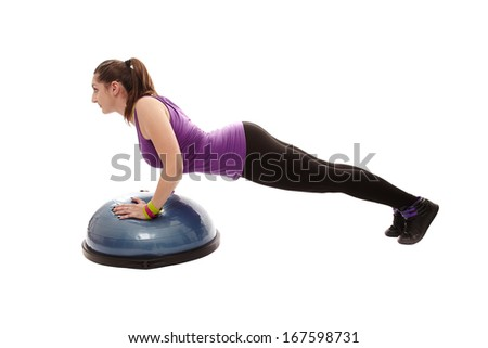 Studio shot of young athletic woman doing pushups on a bosu ball, isolated over white background - stock photo