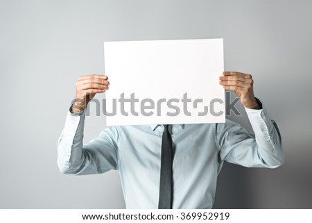 Studio shot of young attractive businessman. Businessman hiding behind blank paper
