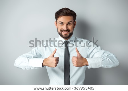 Studio shot of young attractive businessman. Happy businessman showing thumbs up - stock photo