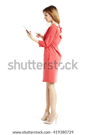 Studio shot of young attractive woman is reading from digital tablet. - stock photo