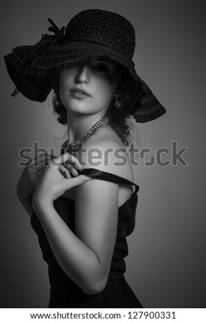 Studio shot of young beautiful woman on dark background in retro style