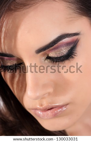 Studio shot of young beautiful woman with professional makeup - stock photo