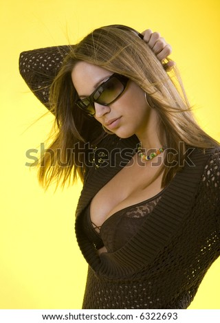 Studio shot of young brunette woman with cleavage exposed - stock photo
