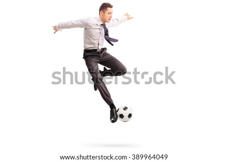 Studio shot of young businessman playing football shot in mid-air isolated on white background - stock photo