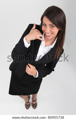 Studio shot of young businesswoman making a telephone sign with hand - stock photo
