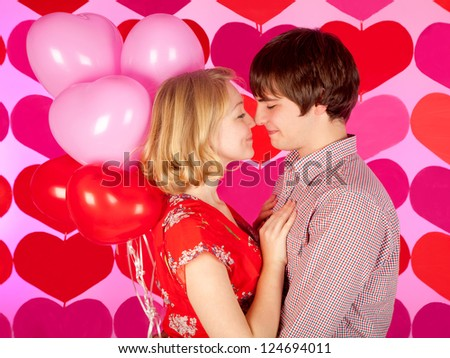 studio shot of young couple in love over colorful background with balloons - stock photo