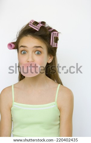 Studio shot of young girl with curlers blowing bubble gum - stock photo