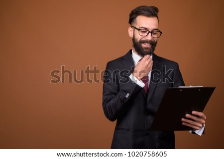 Studio shot of young handsome bearded Persian businessman wearing eyeglasses against brown background