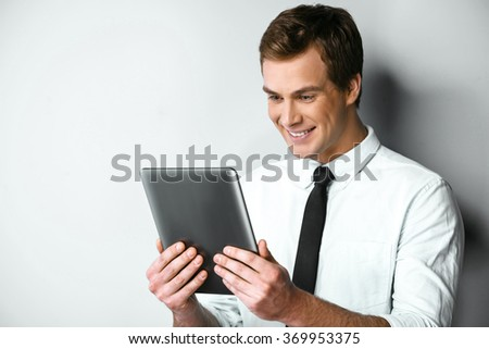 Studio shot of young handsome businessman. Businessman smiling, looking at camera and holding tablet computer - stock photo
