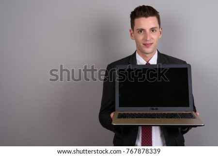Studio shot of young handsome businessman wearing suit against gray background