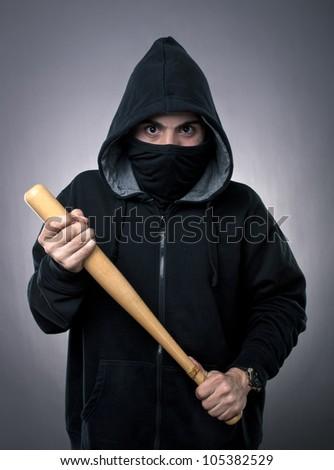Studio shot of  young hooligan with baseball bat on gray background - stock photo