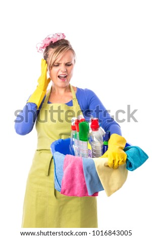 Studio shot of young housekeeper holding bowl full of cleaning  products over white.
