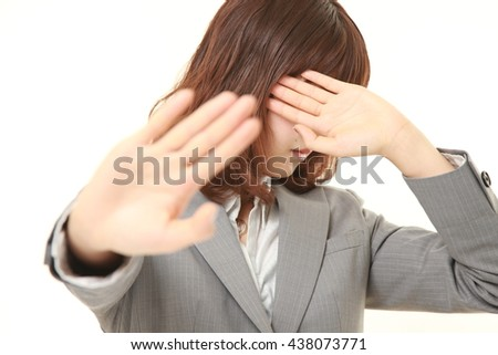 studio shot of young Japanese businesswoman wearing gray suits making stop gesture - stock photo