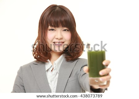 studio shot of young Japanese businesswoman wearing gray suits with green vegetable juice