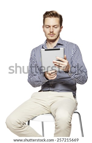 Studio shot of young man working on tablet. - stock photo