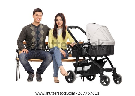 Studio shot of young parents sitting on a wooden bench with a baby stroller beside them isolated on white background