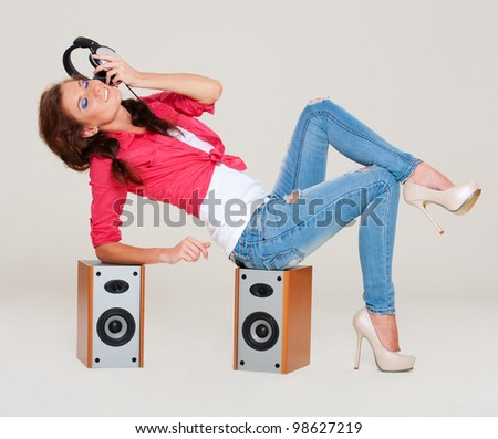 studio shot of young woman listening the music. grey background - stock photo