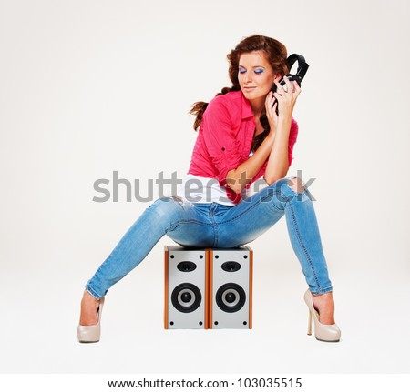 studio shot of young woman listening the music. over grey background - stock photo