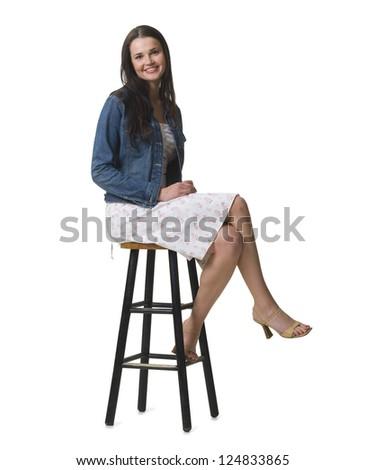 Studio shot of young woman sitting on bar stool - stock photo
