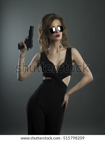 studio shot on dark background young beauty woman holding gun in hand