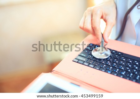 Studio shot over white of a brunette woman listening to her laptop through a stethoscope to see if there are any signs of life - stock photo