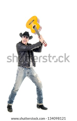 studio shot pictures on isolated background of a rocker man breaking a guitar - stock photo