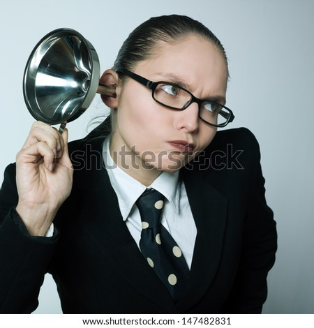 studio shot portrait of one caucasian curious business woman  hearing aid funnel curious spying gossip - stock photo