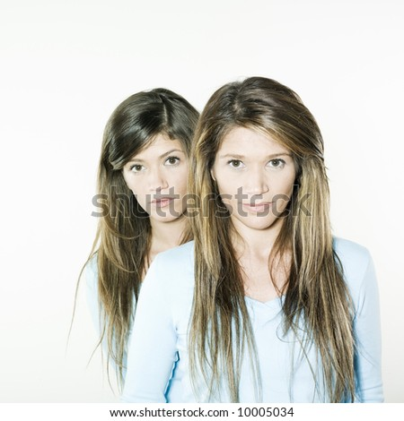 studio shot portrait on isolated background of two sisters twins women friends