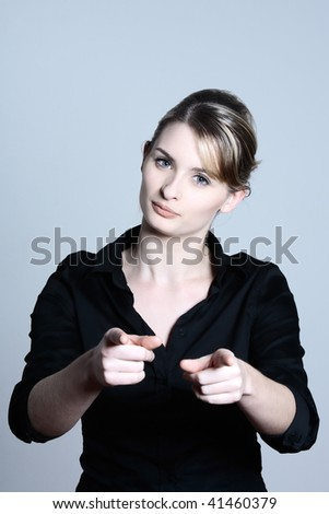 studio shot portraits of a young and cute and expressive woman on a blue grey background pointing his finger - stock photo
