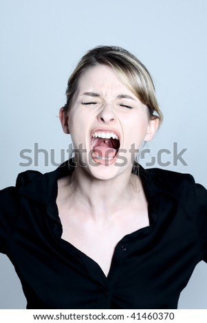 studio shot portraits of a young and cute and expressive woman screaming on a blue grey background - stock photo