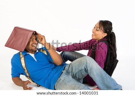 Studious, attractive teen couple flirting.  The young man is lounging on the ground with a folder on his head.  The young woman, who is sitting on the ground, is looking at him laughing. - stock photo