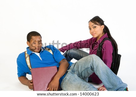 Studious, attractive teen couple wearing backpacks and holding books lying on the ground. - stock photo