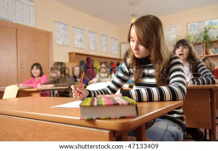 Studious girl is making notes during lesson - stock photo