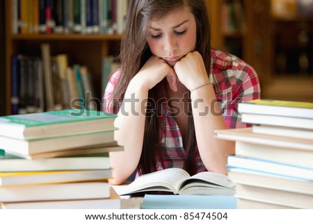 Studious woman surrounded by books in a library - stock photo