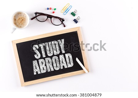 STUDY ABROAD word on Chalkboard with Coffee Cup, view from above - stock photo