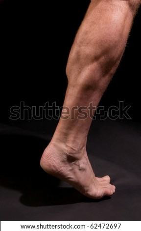 Study: athletic man's calf muscles, against black - stock photo