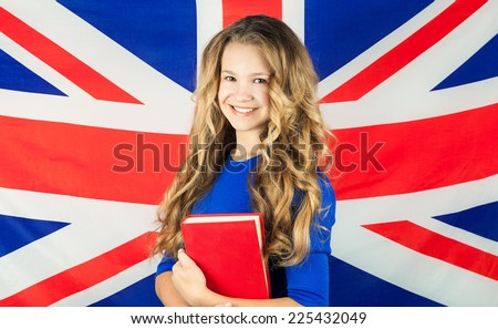 study English. Beautiful cute school girl holding book. Young woman standing with the UK flag in the background looking up. - stock photo