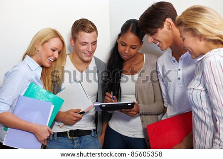 Study group in university hall looking at assignments - stock photo