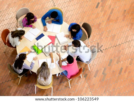 Study group with young people sitting in a round table - stock photo