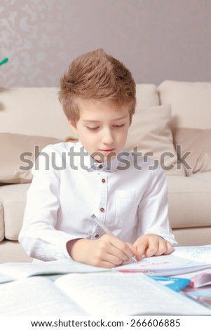 Study hard. Vertical shot of a small cute schoolboy doing writing in his exercise book at home - stock photo