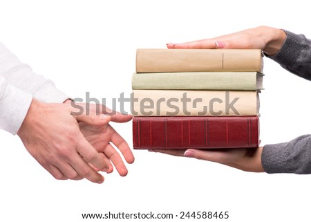 Study material. Closeup of man hands passing a heap of books to young woman isolated on white background - stock photo