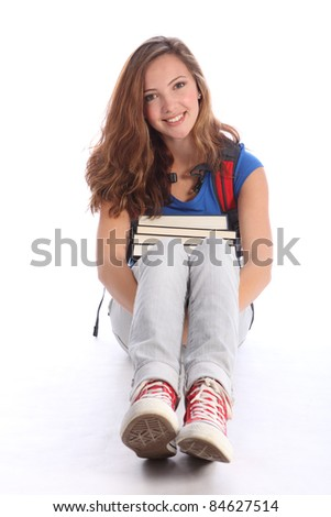 Study time for beautiful high school teenage student girl holding education books sitting on floor, with long brown hair wearing blue t-shirt, jeans and red sneakers and red school backpack. - stock photo