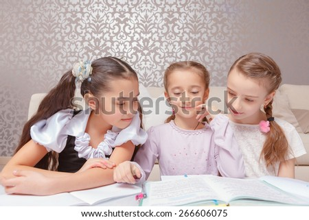 Study together. Three small girls in white and pink looking attentively at the books on the table - stock photo