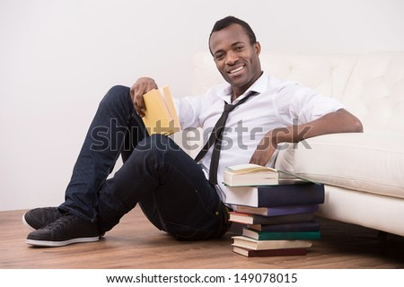 Studying at home. Cheerful African descent men sitting on the floor near the book stack and smiling at camera