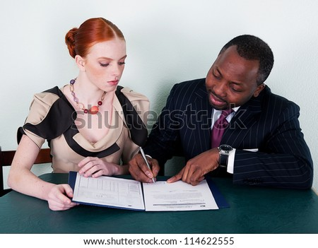 Studying - black american man and red head young girl sitting with documentation - stock photo