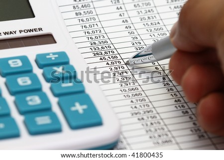 Studying Financial Numbers On A Printed Spreadsheet.